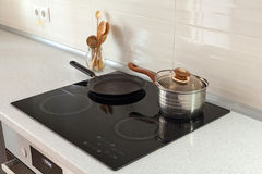 Abra el cazo, la cacerola y las cucharas de madera en cocina moderna con la estufa de la inducción Imagenes de archivo