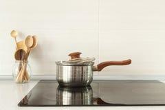 Abra el cazo y las cucharas de madera en cocina moderna con la estufa de la inducción Fotos de archivo libres de regalías