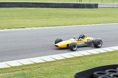 Abra el coche de competición amarillo de la carlinga que conduce en pista Fotografía de archivo