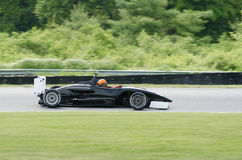 Abra el coche de competición negro de la carlinga que conduce en pista Imagen de archivo libre de regalías