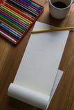 Abra el cojín del gráfico con el lápiz, lápices del color y una taza de café encendido Imagenes de archivo