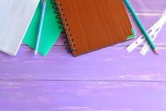Abra el cuaderno, carpeta para los papeles, libreta marrón, lápiz, dos ficheros, pluma en fondo de madera con el lugar en blanco  Imágenes de archivo libres de regalías