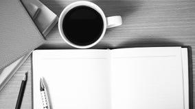 Abra el cuaderno con color blanco y negro de la taza del libro y de café en Imagen de archivo