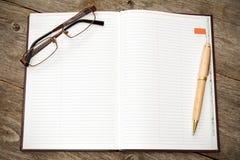 Abra el cuaderno con la pluma y los vidrios Fotos de archivo libres de regalías