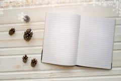 Abra el cuaderno con las páginas en blanco, al lado de conos del pino sobre t de madera Imágenes de archivo libres de regalías