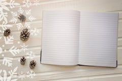 Abra el cuaderno con las páginas en blanco, al lado de conos del pino sobre t de madera Fotos de archivo libres de regalías