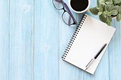 Abra el cuaderno con las páginas en blanco, taza de café y las lentes en la tabla de madera del escritorio, visión superior o end Imagen de archivo