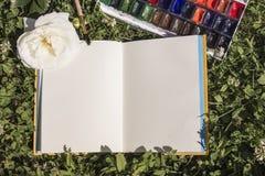Abra el cuaderno con las páginas vacías en un fondo verde natural del trébol Vintage, opinión superior del concepto creativo con  Imagenes de archivo