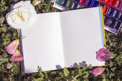 Abra el cuaderno con las páginas vacías en un fondo verde natural del trébol Vintage, opinión superior del concepto creativo con  Fotos de archivo libres de regalías