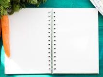 Abra el cuaderno con las páginas en blanco en la tabla verde Fotografía de archivo libre de regalías