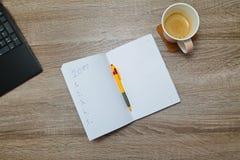Abra el cuaderno con los PLANES POR EL AÑO 2017 y una taza de café en fondo de madera Fotografía de archivo libre de regalías