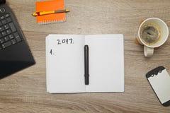 Abra el cuaderno con los PLANES POR EL AÑO 2017 y una taza de café en fondo de madera Imagen de archivo