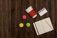 Abra el cuaderno con un lápiz, macarrones, tazas de papel y una tarjeta de crédito en un fondo de madera Imagen de archivo