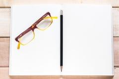 Abra el cuaderno, el lápiz y las lentes en la tabla de madera Imagenes de archivo
