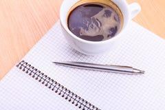Abra el cuaderno en blanco con la taza de café en la tabla Fotografía de archivo libre de regalías