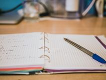 Abra el cuaderno en blanco en la tabla con la pluma Fotos de archivo