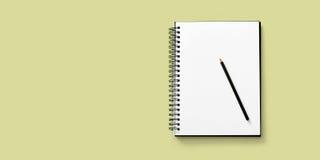 Abra el cuaderno en el fondo blanco con un lápiz Fotos de archivo