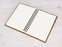 Abra el cuaderno en fondo de madera Imagenes de archivo