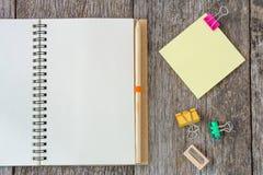 Abra el cuaderno en fondo de madera con el clip de papel y amarillee ningún Fotos de archivo libres de regalías