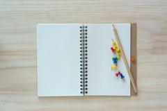 Abra el cuaderno en fondo de madera con la pluma Foto de archivo