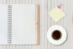 Abra el cuaderno en fondo de madera con la taza de café y amarillee ningún Fotos de archivo