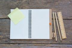Abra el cuaderno en fondo de madera con los lápices y la regla Fotos de archivo