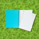 Abra el cuaderno en las hojas verdes Imagen de archivo
