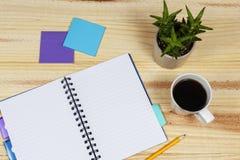 Abra el cuaderno en una tabla con un cactus en conserva Imagen de archivo