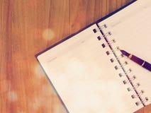 Abra el cuaderno en una tabla de madera con color del filtro del vintage Fotografía de archivo libre de regalías