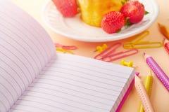 Abra el cuaderno, lápices coloreados, queque de frutas con las bayas en el fondo imágenes de archivo libres de regalías