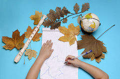 Abra el cuaderno, la flauta, el globo, las hojas de otoño y las manos de la muchacha caucásica Foto de archivo
