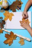 Abra el cuaderno, la flauta, el globo, las hojas de otoño y las manos de la muchacha caucásica Fotografía de archivo