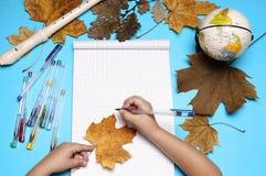 Abra el cuaderno, la flauta, el globo, las hojas de otoño y las manos de la muchacha caucásica Imágenes de archivo libres de regalías
