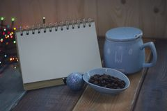 Abra el cuaderno, la taza azul y el grano de café en un cuenco en el tablenn Foto de archivo