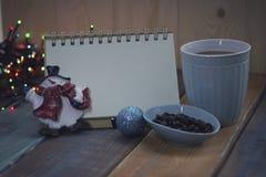 Abra el cuaderno, la taza azul y los granos de café en el tablen Foto de archivo