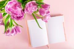 Abra el cuaderno para escribir sueños e ideas con las flores próximas Foto de archivo libre de regalías