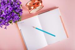 Abra el cuaderno para escribir sueños e ideas con las flores próximas Foto de archivo