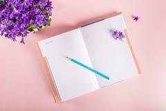Abra el cuaderno para escribir sueños e ideas con las flores próximas Imagen de archivo