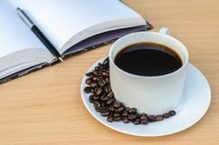 Abra el cuaderno, Pen And Cup Of Coffee en la tabla de madera Imagen de archivo libre de regalías