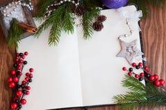 Abra el cuaderno, una hoja de papel con los juguetes de la Navidad, las bayas y las ramitas spruce en un fondo de madera Foto de archivo libre de regalías