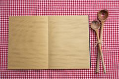 Abra el cuaderno, utensilios de madera de la cocina en el mantel rojo, visión superior, espacio de la copia imagenes de archivo