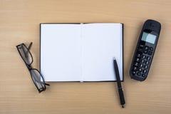 Abra el cuaderno y el teléfono negro en textura de madera Imagen de archivo