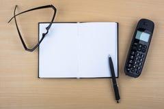 Abra el cuaderno y el teléfono negro en textura de madera Foto de archivo libre de regalías
