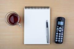 Abra el cuaderno y el teléfono negro en textura de madera Imágenes de archivo libres de regalías