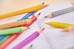 Abra el cuaderno y los lápices coloridos imagen de archivo