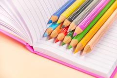 Abra el cuaderno y los lápices coloridos en él imagenes de archivo