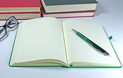 Abra el cuaderno y los libros Foto de archivo libre de regalías
