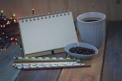 Abra el cuaderno y una taza de café en el tablenn Imagen de archivo libre de regalías