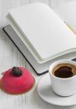 Abra el cuaderno y una taza de café y de torta en el backgro de madera Fotografía de archivo