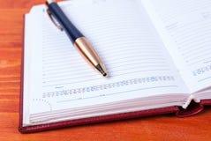 Abra el diario con la pluma que miente en una tabla de madera Imagenes de archivo